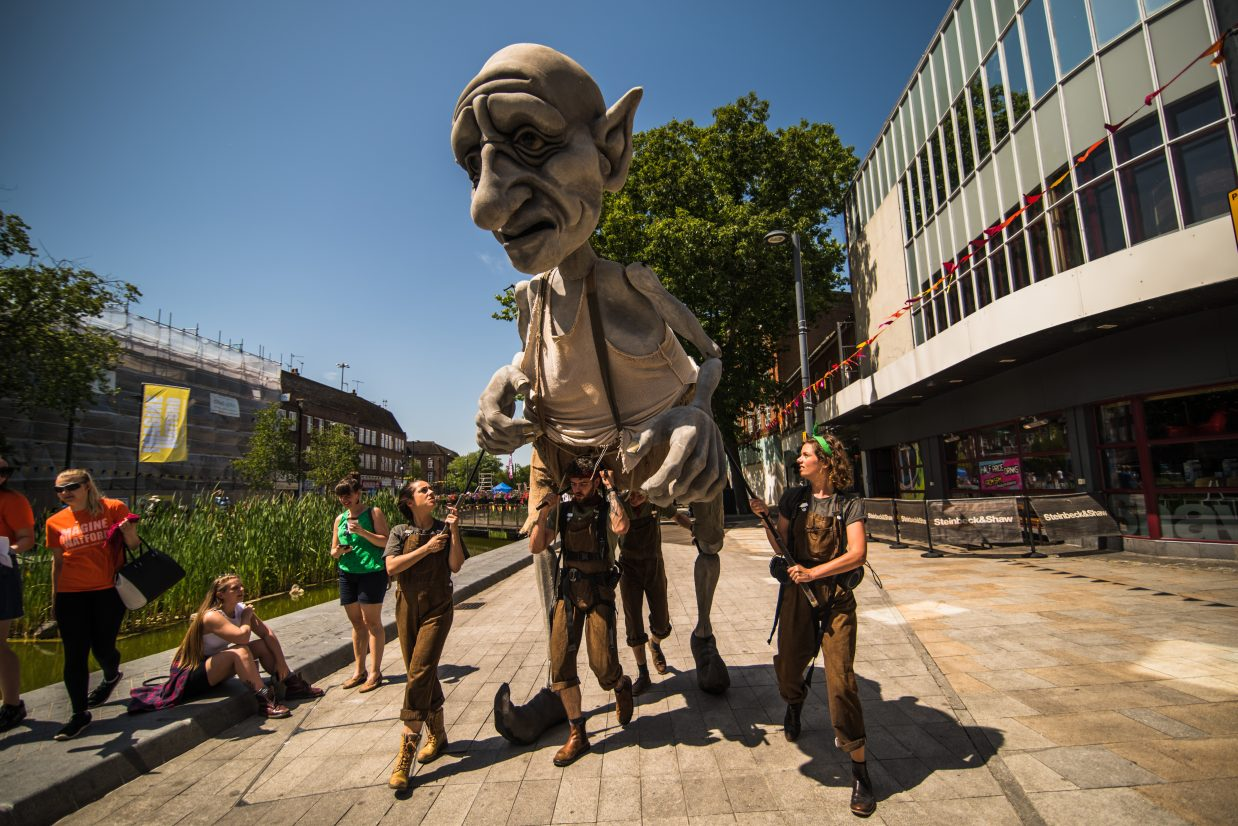 Photo from Imagine Watford. Performers in overalls bear a giant puppet of a goblin-like creature along Watford High Street, heading towards the camera.