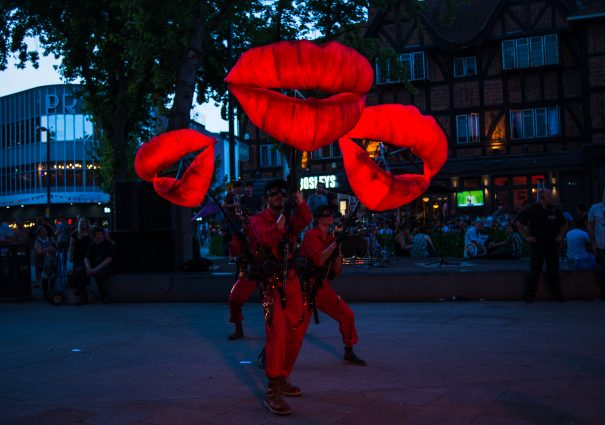 The photo was taken at night time on Watford Hight street as part of the Imagine Watford festival. It shows three performers in red boiler suits holding giant glowing lips.