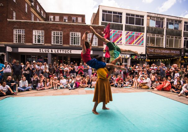 Still image from an Imagine Watford performance. Three performers in bright clothing are in the middle of a mat. One performer holds up the other two, who are also supporting each other. A crowd of onlookers are in the background. The shops lining Watford High Street are visible behind the audience.