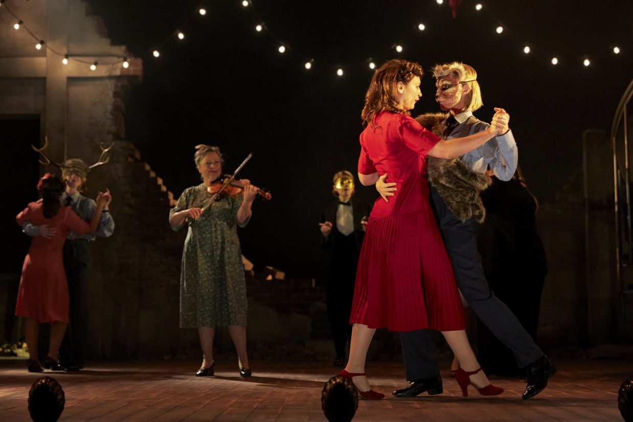 Production photo from the all female production of Much Ado About Nothing. The photo is taken straight on and shows the stage with a false, half destroyed brick wall in the background with a festoon of white lights hanging from the ceiling. On the stage there are 2 couples dancing, a violinist playing and a character in the background wearing a tuxedo and a gold mask.